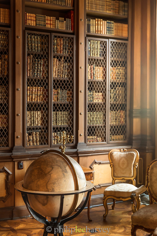 View of library interior with books and globe, interior of Miramare Castle, Trieste, Italy