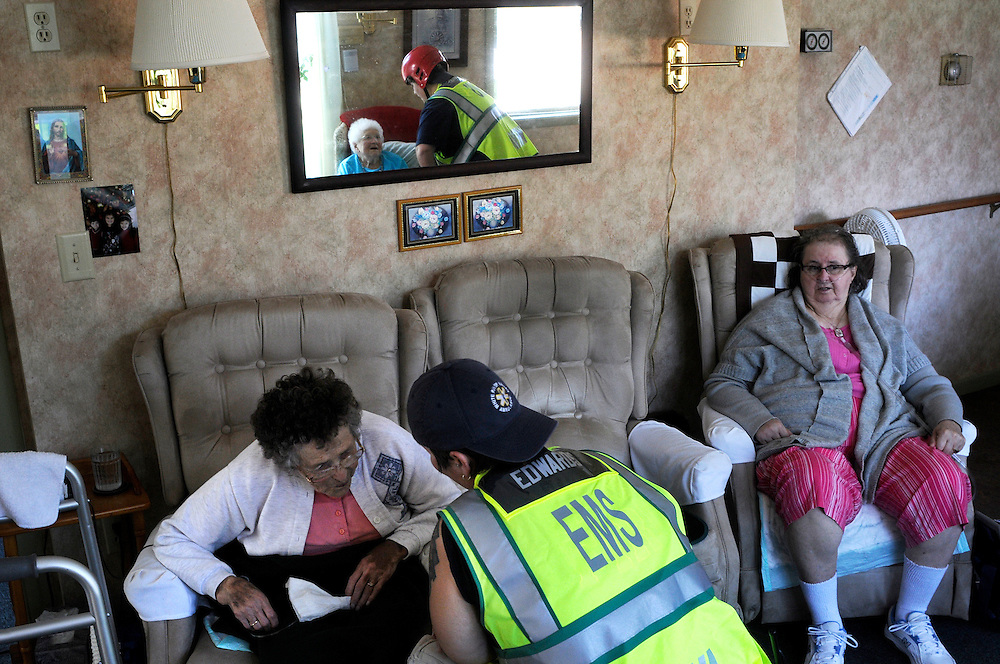 Sasha Edwards, foreground, and Pat Edwards, reflected in mirror, both of White River Valley Ambulance check on Annie Geiko, left, Marion Whitcomb, in mirror, and Susan King, all residents of Johnson's Care Home in Hancock Tuesday, August 30, 2011. The team of Bethel first responders brought bottled oxygen, prescription medications and other medical supplies to Rochester and Hancock Vt. after flooding cut off all paved routes to the towns. <br /> Valley News - James M. Patterson<br /> jpatterson@vnews.com<br /> photo@vnews.com