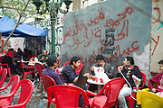 Young men sit at pavement cafe called the Revolution of the 25th of January in the Bourse area of Cairo.  Cairo, Egypt