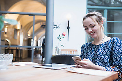 Smiling young woman messaging on mobile while sitting at restaurant