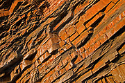 Aview of diagonally dsipping rock strata with sedimentary layers
