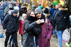 © Licensed to London News Pictures. 21/12/2019. London, UK. A couple takes a selfie as fake snow falls on London's Oxford Street. Retailers are expecting a rush of shoppers in the lead-up to Christmas. Photo credit: Dinendra Haria/LNP