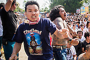 "23 MARCH 2013 - NAKHON CHAI SI, NAKHON PATHOM, THAILAND:Men rush the stage at the close of the Wat Bang Phra tattoo festival. Wat Bang Phra is the best known ""Sak Yant"" tattoo temple in Thailand. It's located in Nakhon Pathom province, about 40 miles from Bangkok. The tattoos are given with hollow stainless steel needles and are thought to possess magical powers of protection. The tattoos, which are given by Buddhist monks, are popular with soldiers, policeman and gangsters, people who generally live in harm's way. The tattoo must be activated to remain powerful and the annual Wai Khru Ceremony (tattoo festival) at the temple draws thousands of devotees who come to the temple to activate or renew the tattoos. People go into trance like states and then assume the personality of their tattoo, so people with tiger tattoos assume the personality of a tiger, people with monkey tattoos take on the personality of a monkey and so on. In recent years the tattoo festival has become popular with tourists who make the trip to Nakorn Pathom province to see a side of ""exotic"" Thailand. The 2013 tattoo festival was on March 23.    PHOTO BY JACK KURTZ"