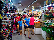 09 JULY 2017 - SINGAPORE: A woman walks through Tiong Bahru market. Tiong Bahru market, in the midst of the Tiong Bahru Housing estate, was the first indoor market in Singapore and is considered one of the best markets in Singapore. It was built in 1955 in an effort to organize vendors and get them off the neighborhood streets. Tiong Bahru neighborhood is now one of the most popular neighborhoods in Singapore for both expats and Singaporeans.    PHOTO BY JACK KURTZ