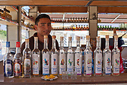 Mexcian man with bottles of mescal for sale in an artisan palenque / distillery. Oaxaca in southern Mexico is known for being the main producer of Mescal, the drink of which Tequila is a type. The Mescal route around the area of Mitla has dozens of artisan distilleries which can be visited to take part in Mescal tasting sessions and to see how they cut the agave cactus and make the drink in the traditional way.