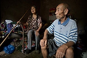 71 year old Hou Guiying and her husband 81 year old Ma Jinling, sitting in their home at a rural village near Fuyang, Anhui Province,  China on 28 August  2013.  As able-bodied adults seek work in cities in hopes of better income, more and more villages in China are inhabited mostly by the elderly and children.