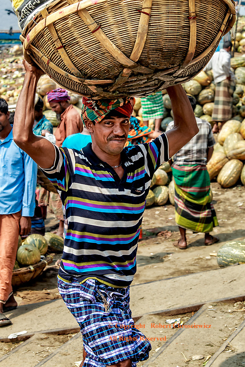 Working Man: A lean man swiftly negotiates a stairway with a basket full of fruit carried atop of his head, Dhaka Banglades
