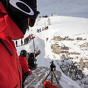 Snowboarder Mark Carter looks on as his North Face Teammate Griffin Post pulls a massive shifty into the couloir.