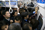 passengers in a very full commuter train during rush hour Tokyo Japan