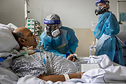 May0098786 . Daily Telegraph<br /> <br /> DT News<br /> <br /> Mohammad Akram an ICU 5 patient with<br /> Specialist Occupational Therapist Jessica Jury . Mohammed had a temporary tracheostomy to assist his airway and needs to write messages on a white board to aid communication with the ICU staff .  <br /> <br /> The Occupational Therapy Team at Northwick Park Hospital are currently rehabilitating four patients on the ICU , getting them back onto their feet and preparing them for life after Covid . <br /> <br /> London 9 February 2021