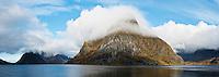 Cloud covered Olstinden mountain peak rises from Kjerkfjord, Reine, lofoten Islands, Norway