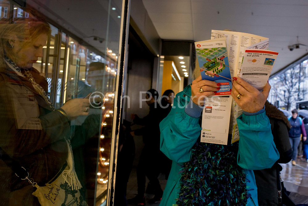 A poor-sighted shopper examines close-up, a map of central London while shopping in Oxford Street. We look at her from a low angle as she holds the folded map of the capital. Her fingers have rings and her nails are painted while another lady stands attending her smartphone. In the background we see shopping crowds entering and leaving the John Lewis department store.