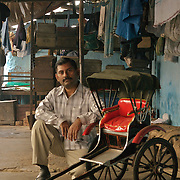 Mr. Anwar Hussain, is the keeper and operator of the rickshaw garage or the 'dera'. here  with the miniature replica that he built. He is now thinking of alternative ways to make a living and wants to start selling the replica rickshaws as suveniers from Kolkata , ..Of the nearly 18,000 pullers, about 75% dwell in 'deras', places where they park their vehicles during the night. These 'deras' belong to the 'sardars' who collect the hand-rickshaws on rental basis from the 'owners', and engage the pullers on different rates. They are the most privileged class in terms of economic viability in this 'owner-sardar-puller' triangle.