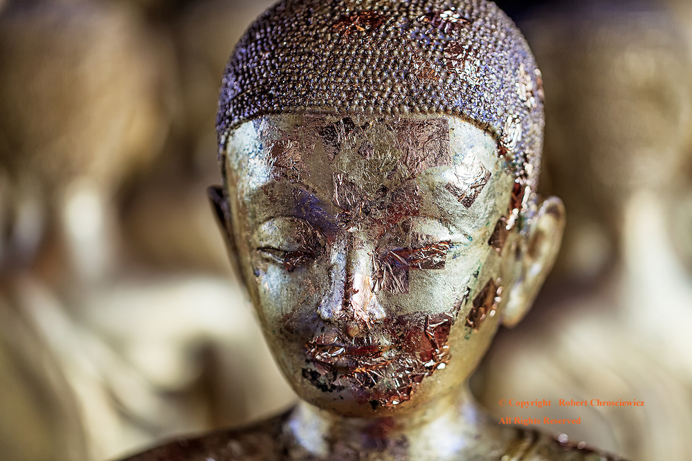 Golden Close-up: A shallow plane of focus reveals the head of a golden Buddha statue with gold foil placed on its face, Wat Thepthidaram Worawihan, Bangkok Thailand.