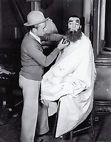 """1929 An MGM make-up artist trims Buster Keaton's beard for his film """"Spite Marriage"""""""