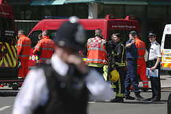 Emergency services head back towards Grenfell Tower after observing a minute's silence near to the tower in west London following a fire which engulfed the 24-storey building on Wednesday morning.