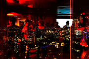 People at a nightime event in a tower block office in Liverpool Street with the city of London in the background. UK.