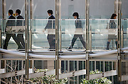 Japanese businessmen walking over modern bridge between office buildings