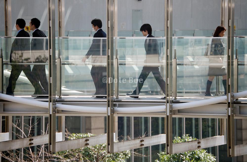 Japanese businessmen walking over modern bridge between office buildings