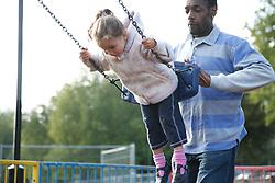 Man  pushing girl on a swing