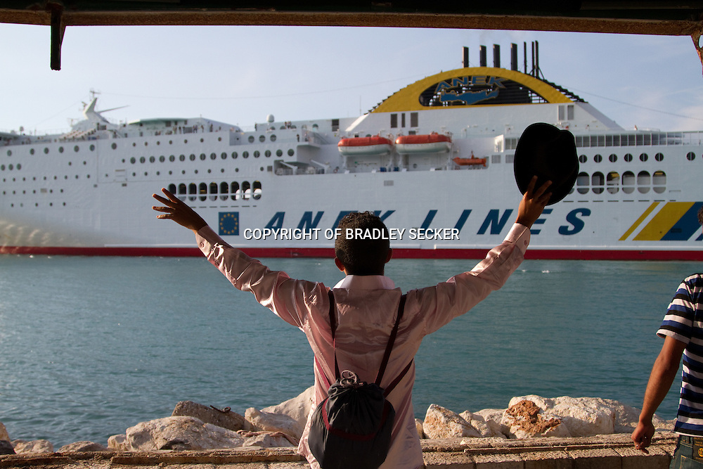 """A migrant from Yemen waves to a passenger ship en route to Italy, and shouts """"No room for one more?!"""". Patras, Greece."""