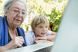 Grandmother and her grandson looking at laptop
