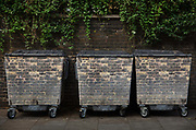 Rubbish bins parked in the highly fashionable Jermyn Street on 19th October 2019 in Londons West End. They are camouflaged with bricks to blend in with the brick wall behind.