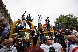 © Licensed to London News Pictures. 09/06/2018. London, UK. 1000s of supporters of EDL founder Tommy Robinson ( real name Stephen Yaxley-Lennon ) on Whitehall for a demonstration in Westminster following Robinson's conviction for Contempt of Court . Robinson was already serving a suspended sentence for Contempt of Court over a similar incident , when he was convicted on Friday 25th May 2018 . Photo credit: Joel Goodman/LNP