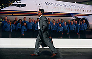 A businessman hurries past a gient Boeing advertising poster during the Farnborough Air Show, England. The poster shows Boeing staff smiling towards the viewer whi;le standing in front of a 737 airliner, specially adapted for business and corporate use, rather than for just economy and premium passengers. The wokforce seem overjoyed to work for this American aircraft manufacturer, grinning to the man who is rushing past their smiling faces without the slightest interest. Farnborough is a world aviation and aerospace trade fair held every two years in Hampshire, England. 2008 will be the 60th year for exhibitors like Boeing to demonstrate and showcase their airliners to the world's aviation industry.