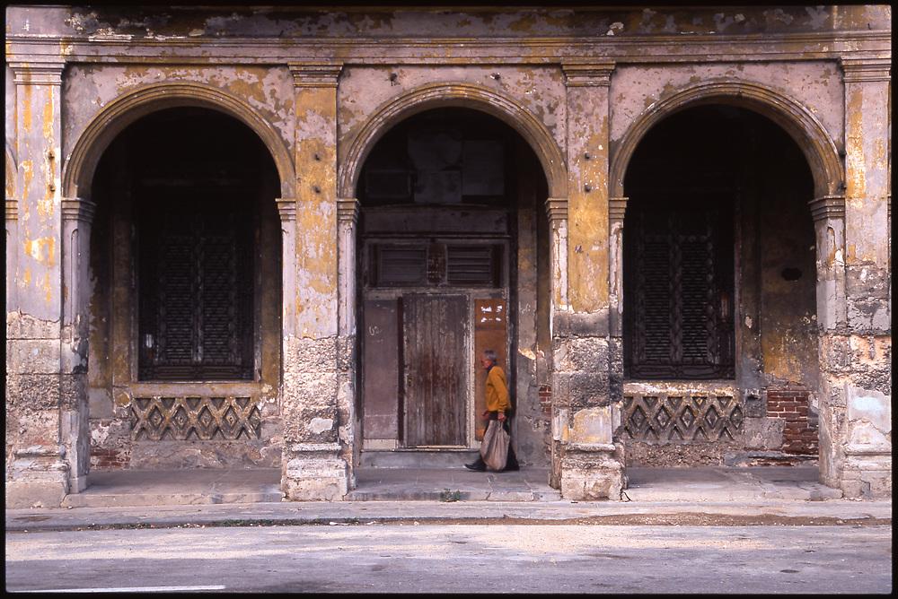 Old Man Walking Past Decayed Building, Havana, Cuba
