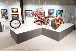 """Josh Soto's Nostalgia, a chopped 1950 Harley-Davidson Panhead with its mid-70s 30"""" over narrowed Denver springer, beside Rick Fairless' Bettie, in the Heavy Mettle - Motorcycles and Art with Moxie exhibition at the Sturgis Buffalo Chip. This is the 2020 iteration of the annual Motorcycles as Art series curated and produced by Michael Lichter. Sturgis, SD, USA. Friday, August 7, 2020. Photography ©2020 Michael Lichter."""