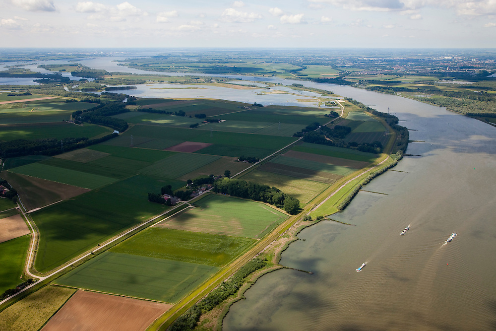 Nederland, Brabant, Gemeente Werkendam, 12-06-2009; polder Noordwaard in de Biesbosch, onderdeel van 'Ruimte voor de Rivier' (bescherming tegen hoogwater door rivierverruiming). Door het gedeeltelijke afgraven van de dijken zijn in- en uitstroomopeningen in de Merwededijk gemaakt (boven in beeld) en is een doorstroomgebied ontstaan waardoor de kans op overstromingen (in de bovenloop) kleiner is. Het deel van de polder wat nu nog landbouwgrond is, onder in beeld, zal in de toekomst ook ontpoldert worden..Polder Noordwaard (part of Biesbosch National Park), part of the program 'Space for the River' (protection against high water by means of creating space for rivers)..Because the dike next to the river has been partly excaveted, entrances for the water of the river have been made (left, above middle). The former polder right of the dike can now store water and allows the river to flood more easily downstream (direction of the Northsea). These mesures dimishes the risk of floods further upstream at high water in the winter..Swart collectie, luchtfoto (25 procent toeslag); Swart Collection, aerial photo (additional fee required).foto Siebe Swart / photo Siebe Swart
