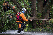 A police officer from Hampshire Police Marine Support Unit assists a tree surgeon working with the National Eviction Team during a large police operation to ensure that protests by environmental activists from HS2 Rebellion did not prevent removal of an ancient alder tree beside the River Colne as part of works connected to the HS2 high-speed rail link on 24th July 2020 in Denham, United Kingdom. Officers from the Metropolitan Police, Thames Valley Police, City of London Police and Hampshire Police attended.