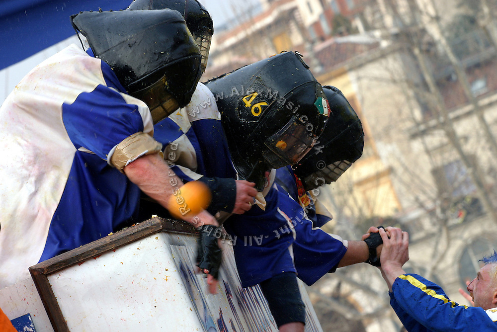 Members of the Credendari (one of the groups fighting from a horse-van, and symbolising the guards of Count Ranieri) are engaged in an open fight during The Battle of the Oranges in Gioberti Square, Ivrea, pop. 30.000. During the days of the Carnival, the town becomes crammed with tourists coming to witness the event which finds its roots at the end of the XII Century, when the people led an insurrection against the local tyrant, Count Ranieri of Biandrate, who was exercising the 'jus primae noctis' rule (having the first night) on the local young brides. The battle to overthrow him is represented with a 3-day-fight between factions in which more then 400 tonnes of oranges are thrown. During the celebrations, food stalls, bands playing music, and parades are also present, giving it a typical Medieval atmosphere. .