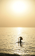 A young teen flips her hair in the water at sunset - Model release available