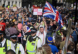 © Licensed to London News Pictures. 31/08/2019. London, UK. A group of Brexit supporters waving the Union Flag are lead through the Pro EU demo by police. Protestors gather near 10 Downing Street and the Houses of Parliament in Westminster, central London to demonstrate as part of a nationwide 'Stop The Coup' day of action against Boris Johnson's plans to suspend parliament. More than 80 demonstrations are planned across the UK in response to government plans to prorogue parliament. Photo credit: Ben Cawthra/LNP