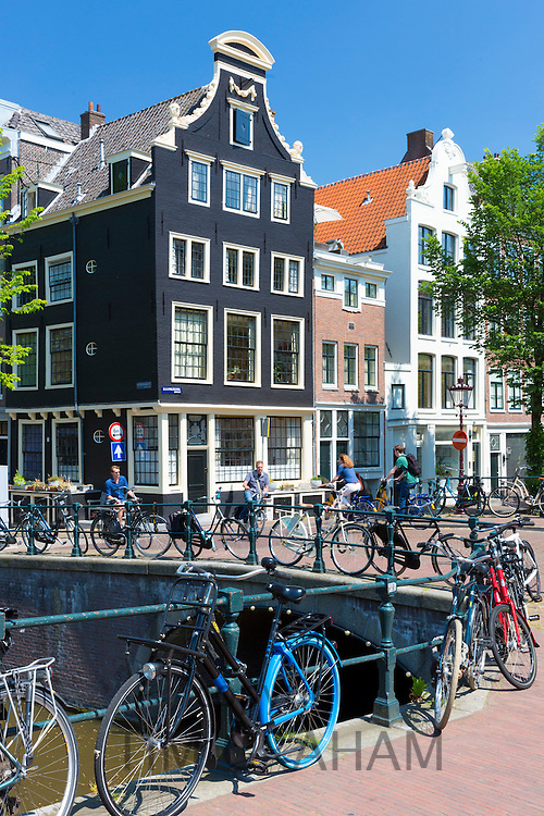 Canalside ornate gabled houses - Dutch gables - and bicycles Herengracht and Blauwburgwal in canal district, Jordaan, Amsterdam