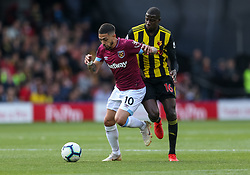 West Ham United's Manuel Lanzini and Watford's Abdoulaye Doucoure during the Premier League match at Vicarage Road, Watford.