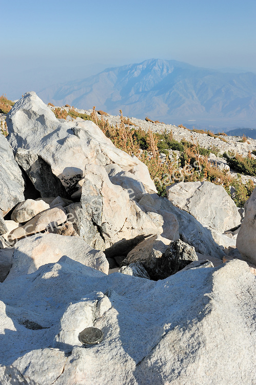 Brass summit marker in lower left, elevation of 11,500 feet.    <br /> <br /> At an elevation of 11,500 feet, granite boulders mark the highest point in Southern California.