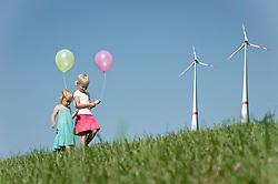 Two girls playing with balloons in windfarm, Bavaria, Germany