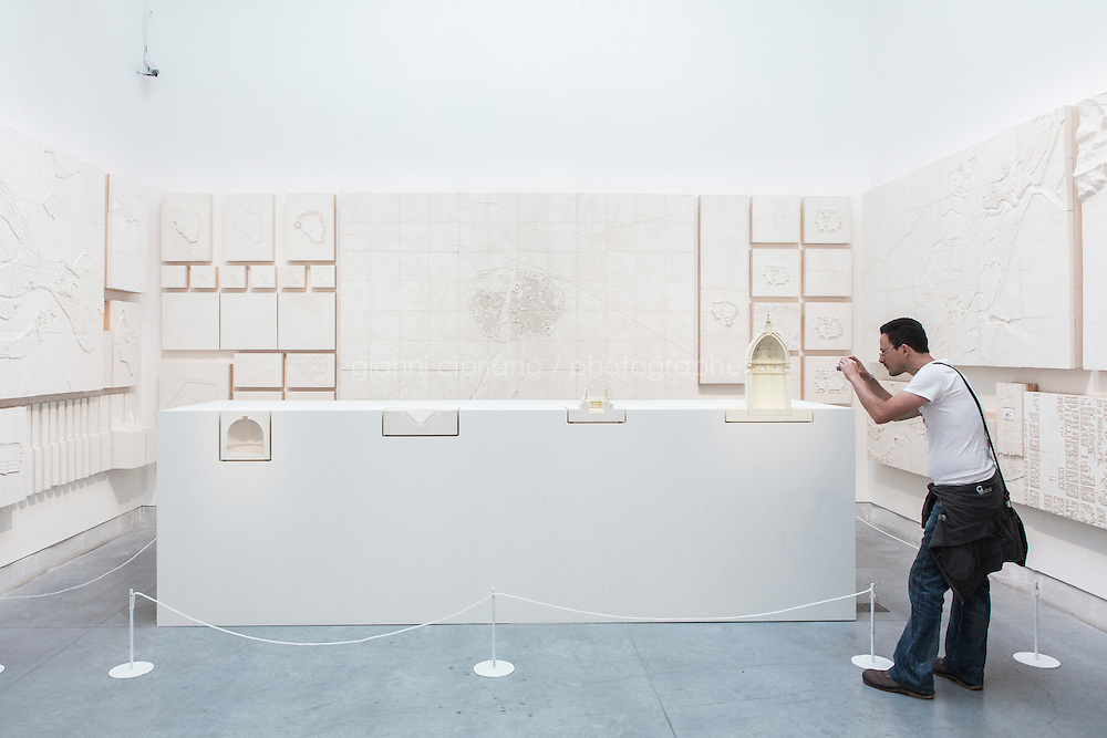 """VENICE, ITALY - 4 JUNE 2016: A visitor photographs the plaster models of Renato Rizzi's """"Orphan Ground"""" exhition are here at the 15th Venice Architecture Biennale in Venice, Italy, on June 4th 2016.<br /> <br /> Rizzi says: """"The four projects in section show us, beyond the concrete needs, the internal movements of invisible powers. The 118 models [of this exhibition] hang on the wall to show us how the matter is the aspiration to soul and vice versa."""