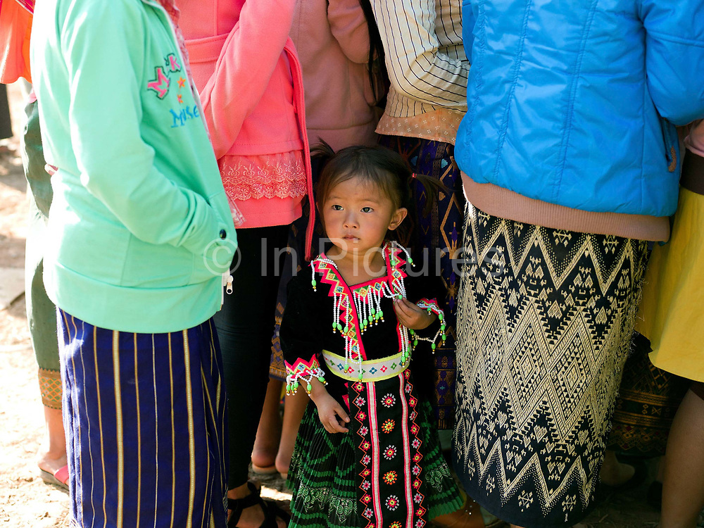 Portrait of a young White Hmong girl wearing contemporary Hmong traditional costume at Ban Hauywai Hmong New Year festival, Phongsaly province, Lao PDR. The Hmong celebration of New Year is based on the lunar calendar. This important time is an opportunity to honour ancestors and spirits through offerings and rituals and to partake in games, sports, feasts, shows, bullfights and courtship. The Hmong are the third largest ethnic group in Laos. One of the most ethnically diverse countries in Southeast Asia, Laos has 49 officially recognised ethnic groups although there are many more self-identified and sub groups. These groups are distinguished by their own customs, beliefs and rituals.