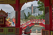 Inside the Chinese pavillion with Longevity Bridge in the background (and modern apartment houses in the far background) at Repulse Bay, Hong Kong Island, China.
