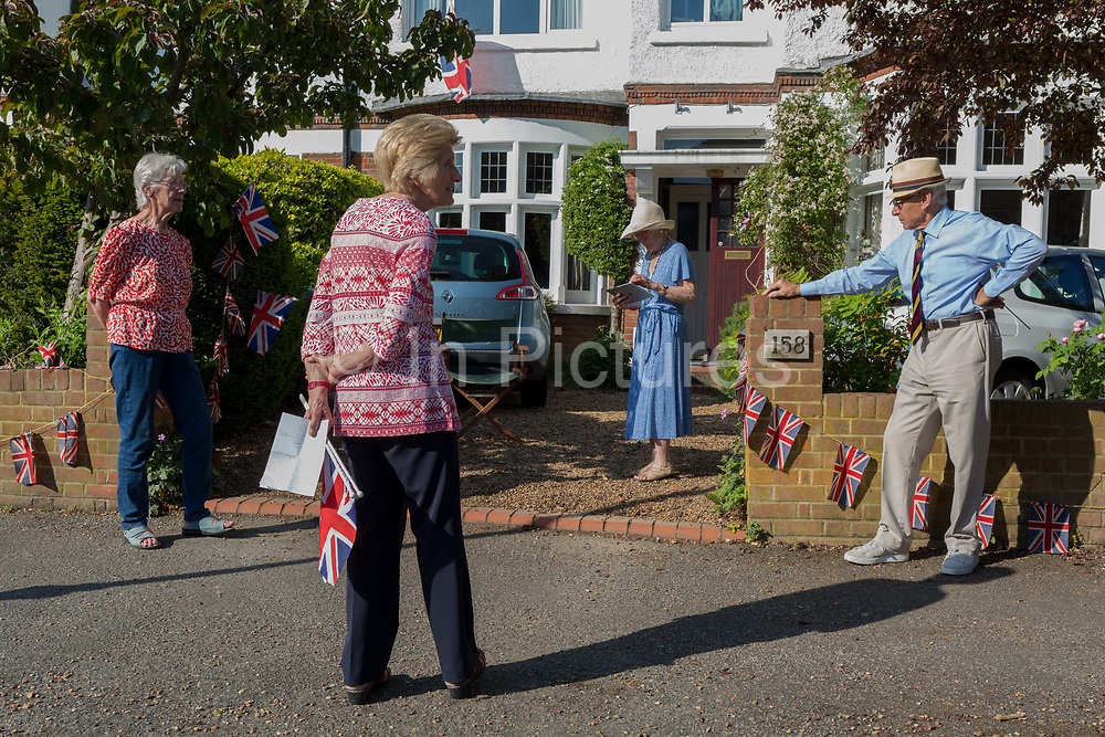 As the Coronavirus lockdown continues over the May Bank Holiday, the nation commemorates the 75th anniversary of VE Day Victory in Europe Day, the day that Germany officially surrendered in 1945 and in Dulwich, neighbours and residents emerge from their homes to party while still observing social distancing rules. Local residents respecting social ditancing, chat after together singing the wartime morale-raising songs of Dame Vera Lynn: White Cliffs of Dover and Well Meet Again, on 8th May 2020, in London, England.