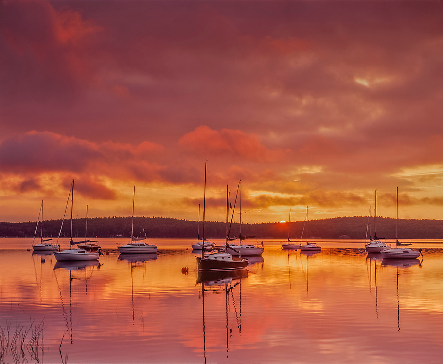 Sunrise colors in clouds & reflections, Lake Massabesic with boats moored, Auburn, NH
