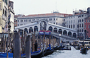 View of gondolas and vaporettos traveling through the Grand Canal with the Rialto Bridge in the background, Venice, Italy. The Rialto Bridge (Italian: Ponte di Rialto) is one of the three bridges spanning the Grand Canal in Venice, Italy. It is the oldest bridge across the canal and probably the most famous in the city...Subject photograph(s) are copyright Edward McCain. All rights are reserved except those specifically granted by Edward McCain in writing prior to publication...McCain Photography.211 S 4th Avenue.Tucson, AZ 85701-2103.(520) 623-1998.mobile: (520) 990-0999.fax: (520) 623-1190.http://www.mccainphoto.com.edward@mccainphoto.com.
