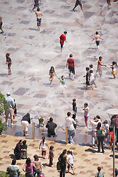 Stock photo of a group of children playing in the fountains on a hot afternoon