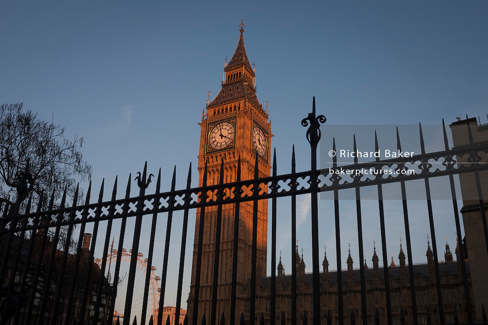 Silhouetted security railings featuring spikes and Elizabeth Tower of the British parliament, on 17th January 2017, in London England. The Elizabeth Tower (previously called the Clock Tower) named in tribute to Queen Elizabeth II in her Diamond Jubilee year – was raised as a part of Charles Barry's design for a new palace, after the old Palace of Westminster was largely destroyed by fire on the night of 16 October 1834. The new Parliament was built in a Neo-gothic style, completed in 1858 and is one of the most prominent symbols of both London and England.