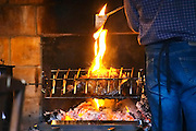 Leg of wild boar roasted, grilled over open fire and char coal, with the chef moisturising it with burning fat. Mas de Perry, Mas Nicot. Terrasses de Larzac. Languedoc. France. Europe.