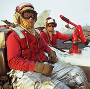 """Two crewmen aboard the US Navy aircraft carrier USS Harry S Truman sit on a fire vehicle on the ship's deck. Wearing red signifies that they are part of a crash and salvage team who respond to emergencies and fire hazards and so wear flame-retardant and anti-flash clothing material. Ordinarily they are responsible for making safe and towing (""""doing the bow dance"""") $38 million F/A-18s fighters round the deck of the Navy?s newest aircraft carrier, here on coalition patrol somewhere off Kuwait in the Arabian Sea. The Truman is so called after the US President who was in office from 1945 to 1953.  Picture from the 'Plane Pictures' project, a celebration of aviation aesthetics and flying culture, 100 years after the Wright brothers first 12 seconds/120 feet powered flight at Kitty Hawk,1903."""